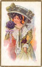 sub000403 - Woman smelling purple flowers wearing a green bonet