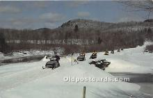 Group of Snowmobiles cross a bridge